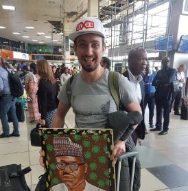 White man pictured with a portrait of Pres. Buhari at the airport, says he likes the Nigerian president and wants to take him to his country