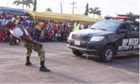 Viral Photos show?Nigerian soldier dragging a?Hilux van, bag of rice using his teeth