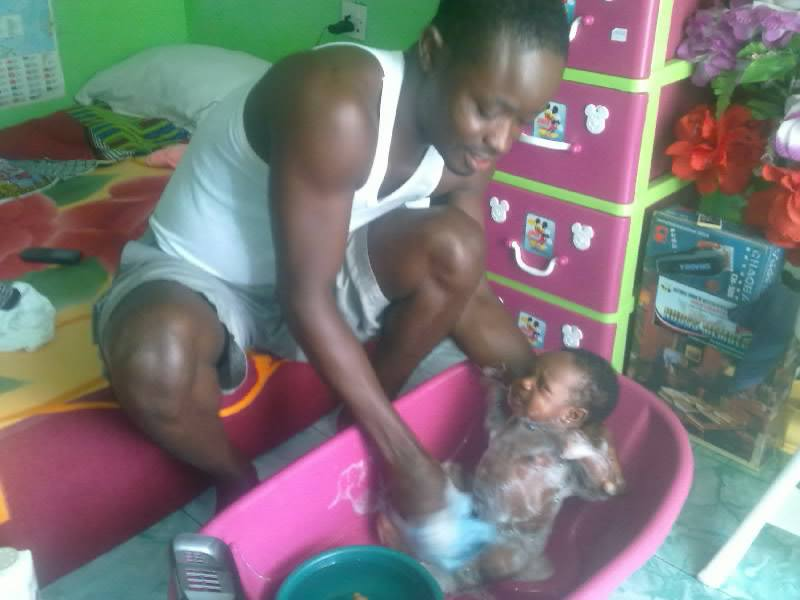 Nigerian man shares photos of himself bathing his newborn baby to advocate for paternity leave