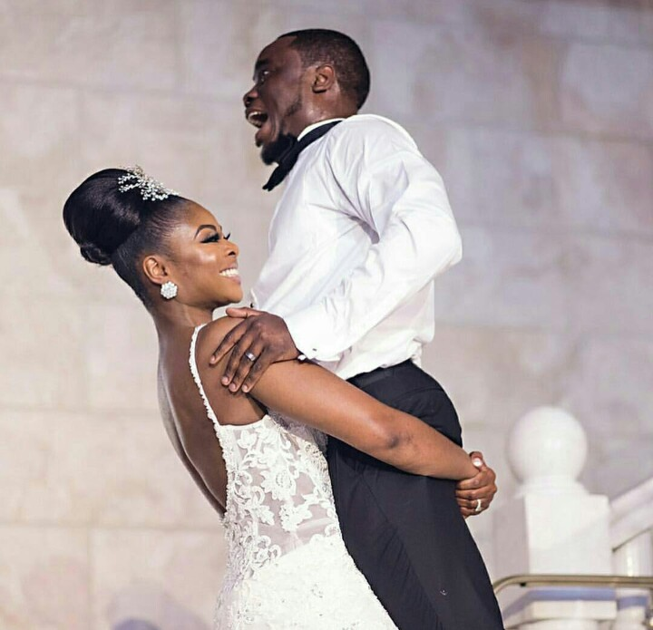 Superwoman bride lifts her husband on their wedding day