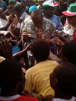 Photos: Former Governor Peter Obi mobbed by traders as he shares money in a market
