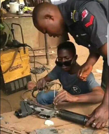Viral photo shows a?Nigerian policeman fixing his faulty gun at a roadside welder