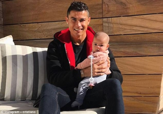 Doting dad! Cristiano Ronaldo cradles his daughter Eva as they pose for a photo.