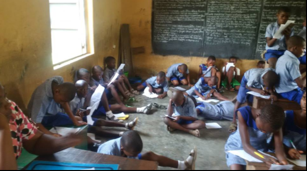 Primary school students pictured lying and sitting on the floor to write their exams in Akwa Ibom state (photos)