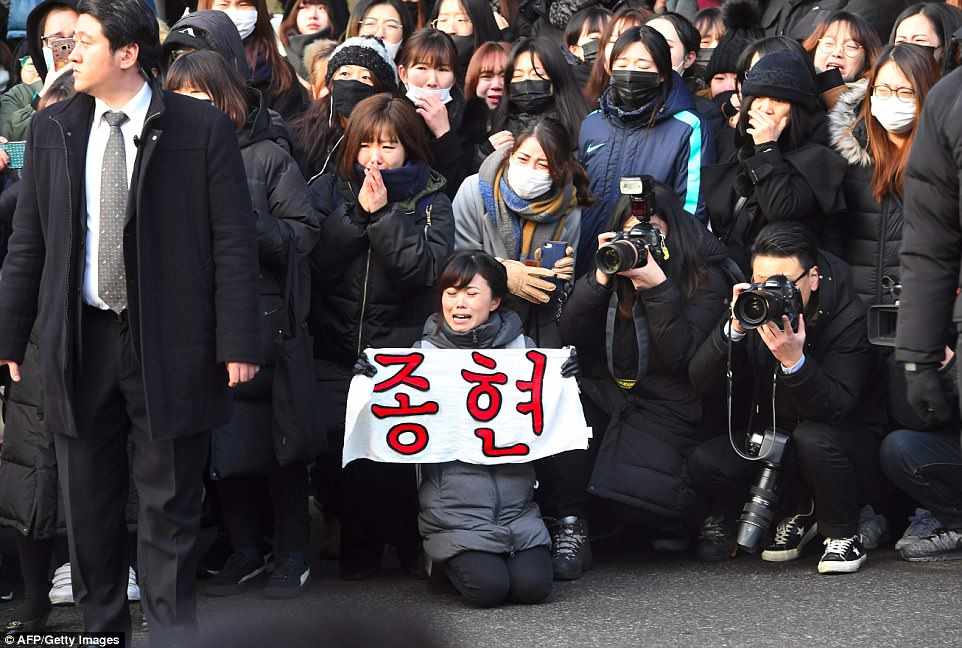 Grieving bandmates of SHINee carry the coffin of their lead singer who killed himself because of