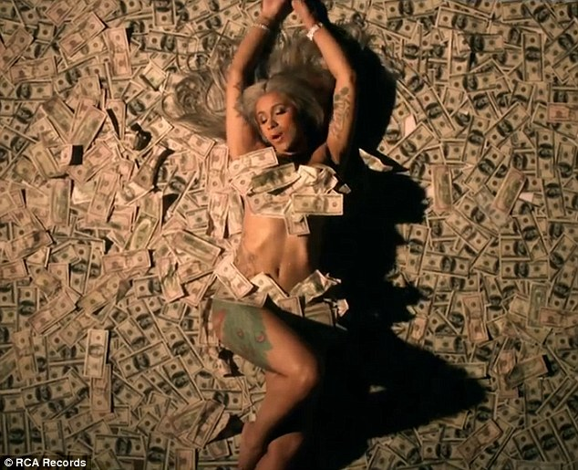 Cardi B covers her nakedness with hundred dollar bills in new video (Photos)