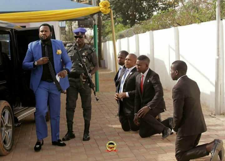 Viral photos of grown men kneeling to welcome their pastor to church in Abuja