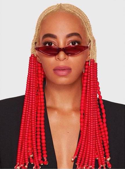 Solange Knowles switches up her hair do, rocks blond braids with lots of red beads.