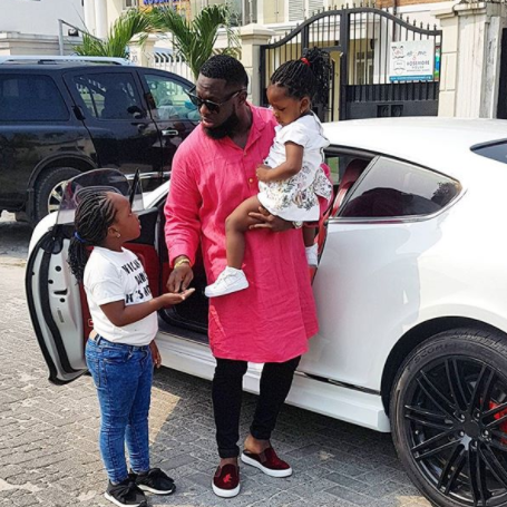 Daddy duties: Timaya pictured on a school run with his daughters