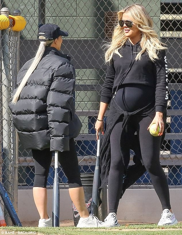 Pregnant Khloe Kardashian cradles her growing bump while watching her sisters play softball with their mom ?(Photos)