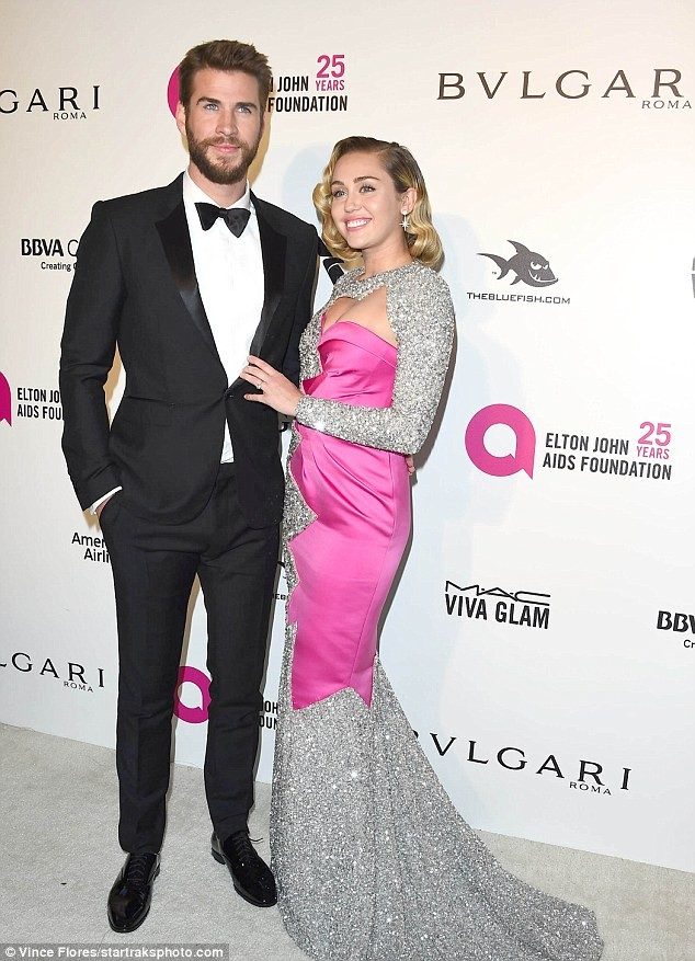 Miley Cyrus wears plunging gold dress to Vanity Fair Oscar Party with fianc? Liam Hemsworth...