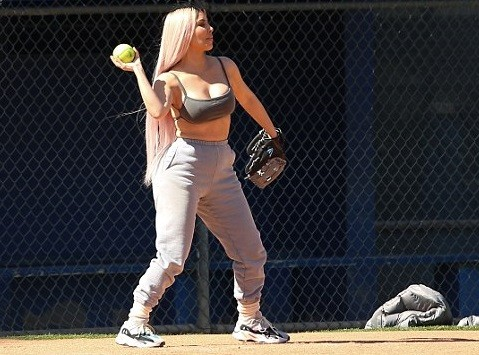 Kim K flaunts her cleavage and flat tummy in sports bra as she joins her famous family for softball game (Photos)
