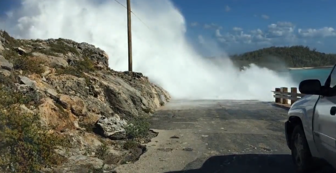 Shocking moment a man was swept off a bridge by giant waves in the Bahamas (video)