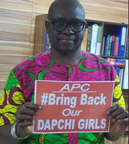 "Governor Fayose carries placard that reads, ""APC, #BringBackOurDapchiGirls"""