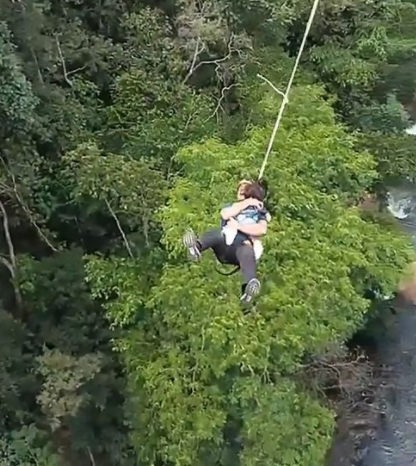 Reckless dad jumps 200ft off bridge in bungee jump stunt while holding toddler daughter (video)