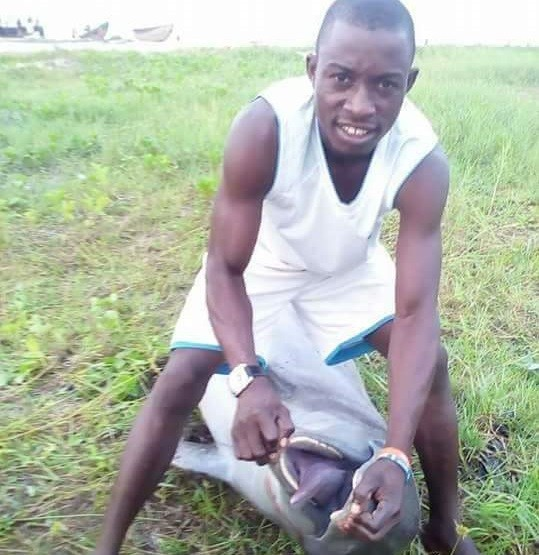 Photos: Man kills a Dolphin in Akwa Ibom State, poses on top of the
