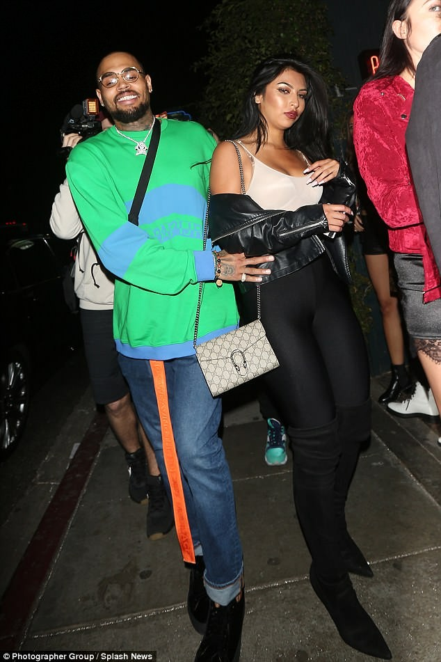Chris Brown places his hands around a curvy mystery woman