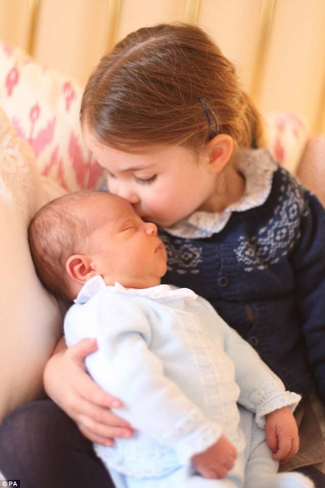Adorable photos taken by Kate of the newborn prince being kissed by his older sister, Charlotte
