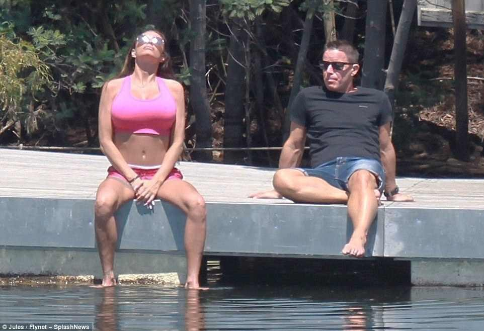 Former glamour model Katie Price goes topless as she soaks up the sun with male pal in Portugal (Photos)