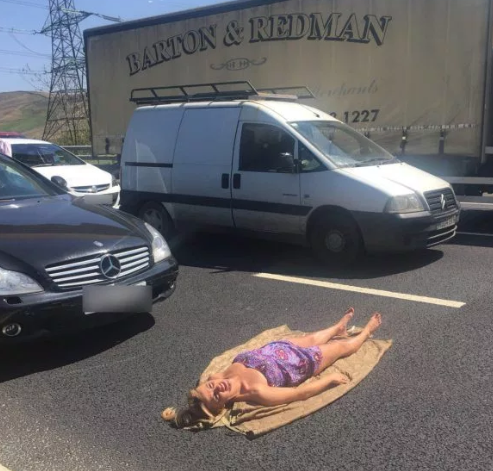 Girl strips off and sunbathes on an expressway while stranded in traffic jam