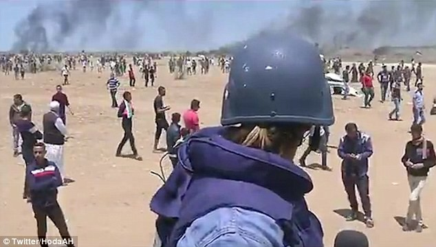Al Jazeera journalist narrowly avoids being shot by a sniper and hit by tear gas grenade as she reports from the front line of Gaza protests