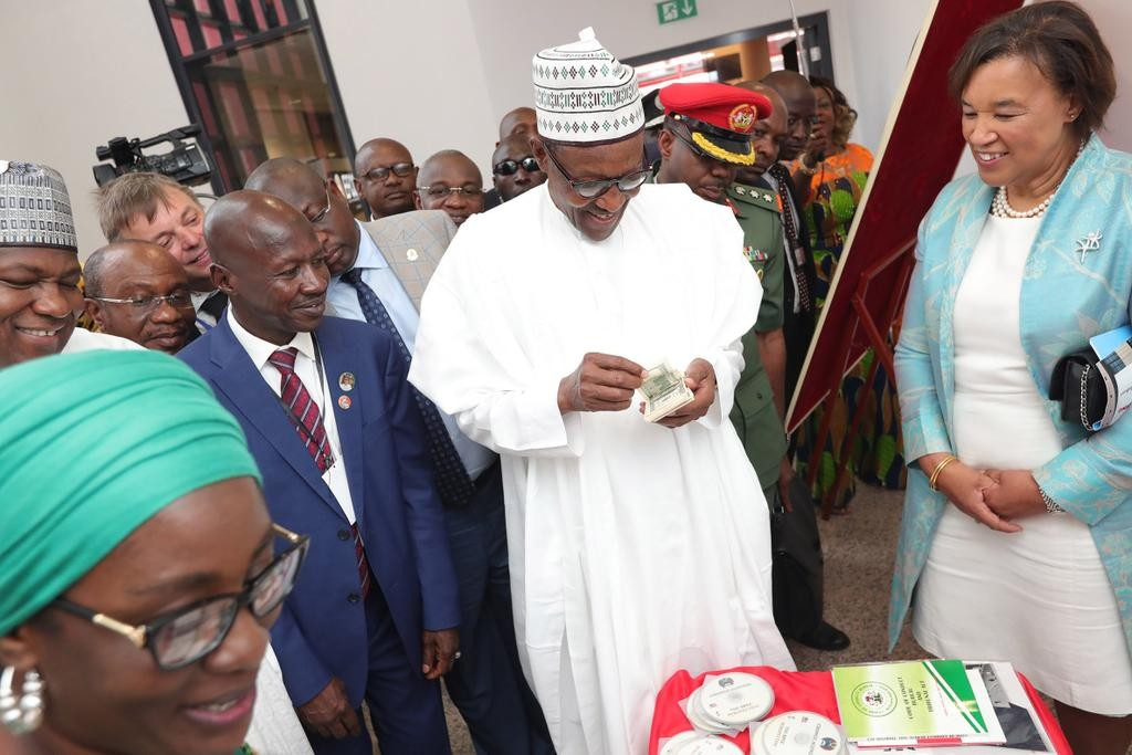 Caption this photo of President Buhari with wads of dollar bills