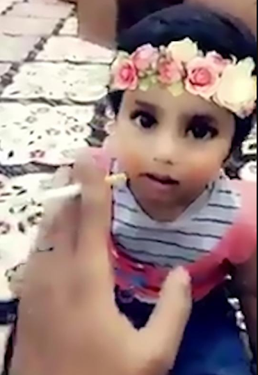 Dad is caught on video teaching his toddler daughter to smoke a cigarette (video)