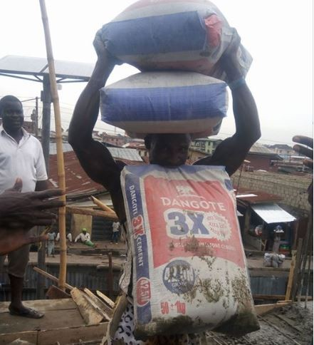 Photo: Nigerian laborer displays rare strength by lifting a bag of cement with his teeth while balancing?two bags on his head