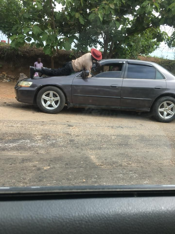 FRSC official jumps on the moving vehicle of a motorist who refused to stop for him(Photos)