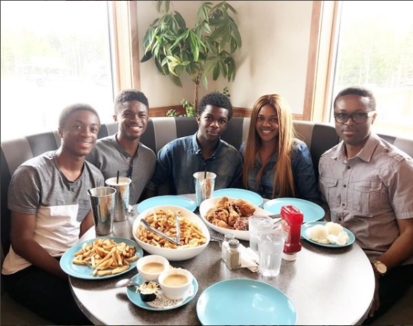 Beautiful family photo of Omoni Oboli, her husband and their handsome sons enjoying dinner together
