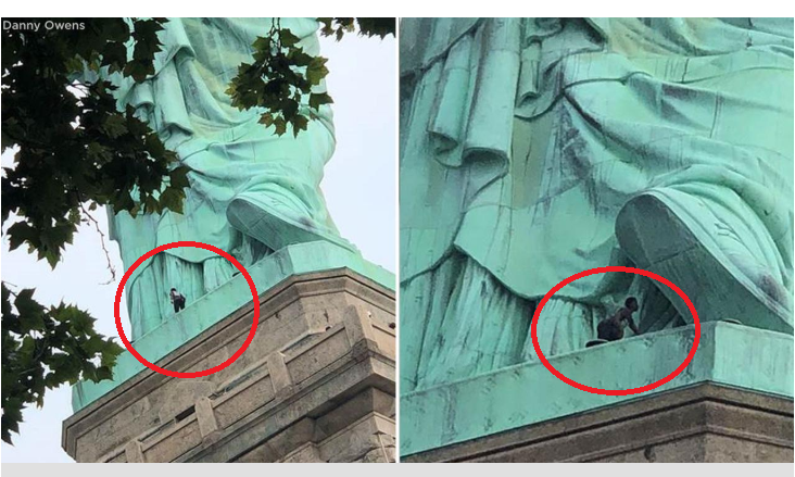 Black woman spotted climbing the statue of liberty (Video)