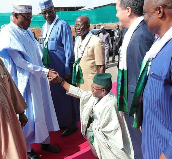 Photo: Governor Nasir El-Rufai kneels to greet President Buhari at the Abuja Metro rail commissioning ceremony