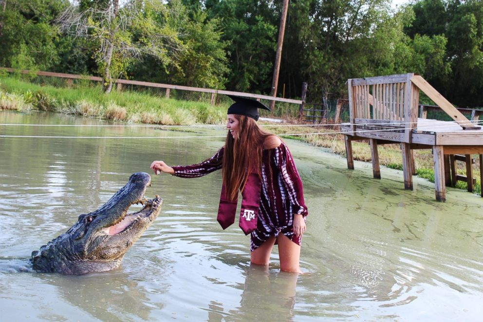 Fearless college student poses with a nearly 14-foot long and 1,000-pound alligator for jaw-dropping graduation photoshoot (Photos)