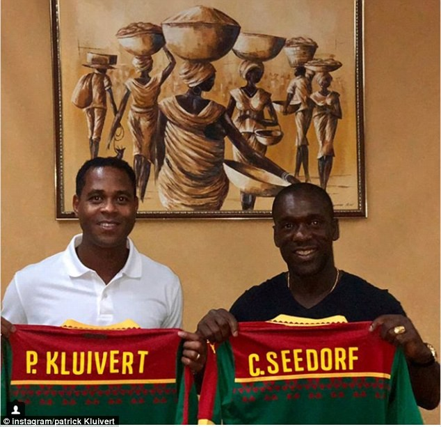 Dutch football legends Patrick Kluivert and Clarence Seedorf pose with Cameroon jerseys after taking charge of national side