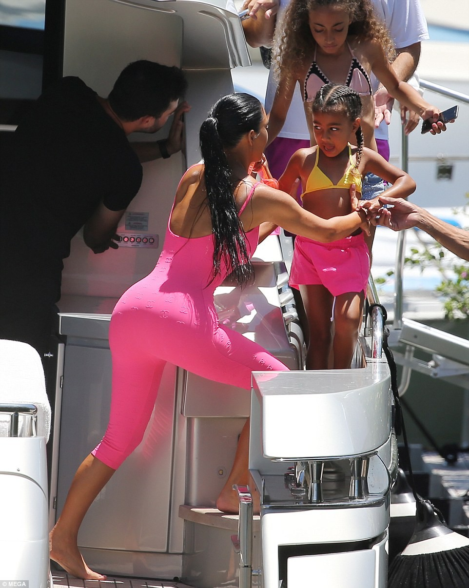 Kim Kardashian flaunts her hourglass figure in sexy playsuit as she goes on a boat trip with Saint and North in Miami (Photos)