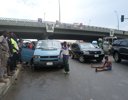 Photo: Half naked passenger sit in middle of busy road in Lagos to protest arrest of bus driver