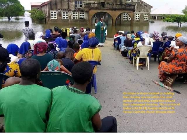 Photos: Christians in Anambra hold Mass in small portion of land around their submerged church