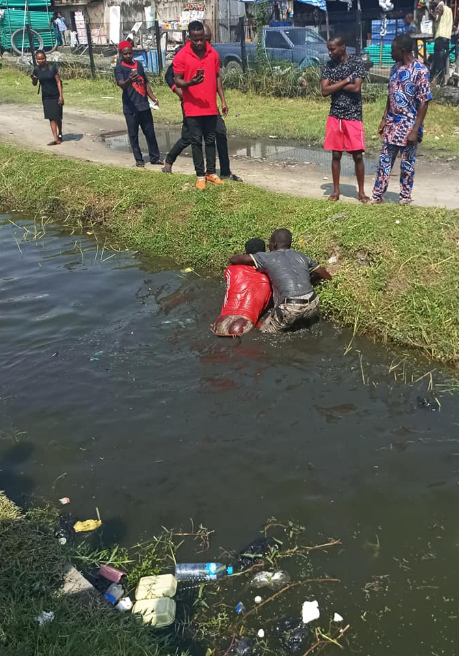 Bus driver and conductor fight inside gutter in Lekki over payment (photos)