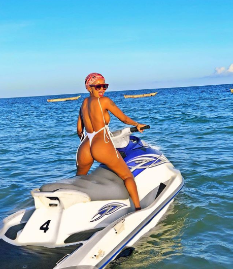 Huddah Monroe shows off her very curvy backside in a swimsuit that leaves little to the imagination (photos)
