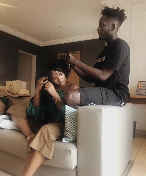 This photo of Mr Eazi helping Temi Otedola losen her hair, has got everyone talking