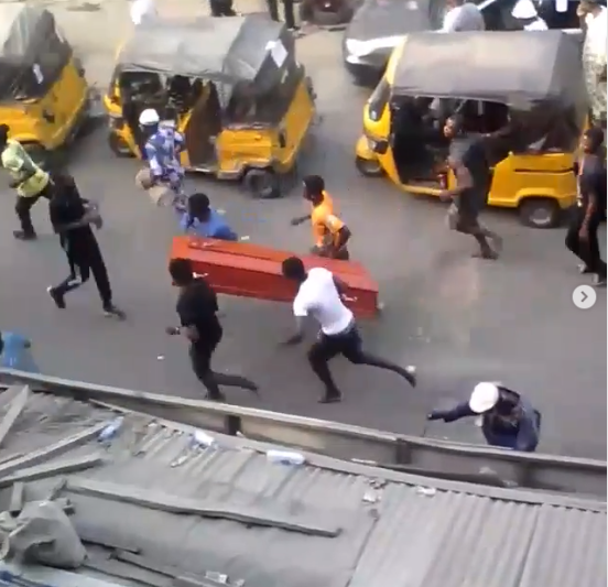 Ikeja residents take to their heels as mourners are filmed swinging a casket while masquerades extort keke and okada riders (video)