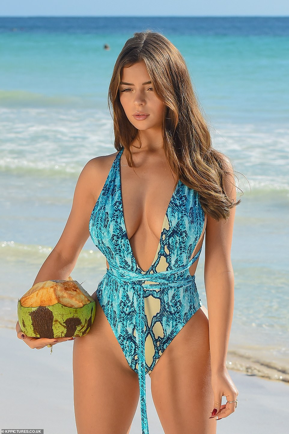 British model, Demi Rose puts on an eye-popping display as she poses in aquamarine snakeskin swimsuit (Photos)