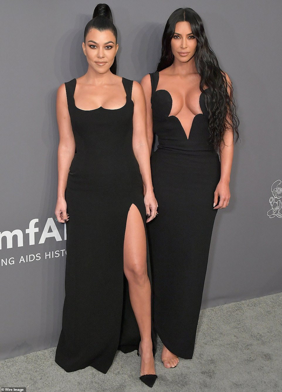 Kim and Kourtney Kardashian flaunts extreme cleavage in glamorous black gowns as they attend amfAR Gala in New York together (Photos)