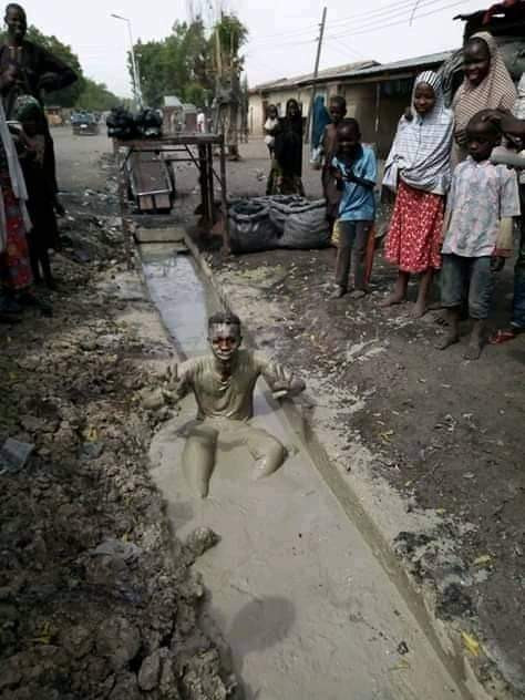 Another man dips himself inside dirty gutter to celebrate President Muhammadu Buhari