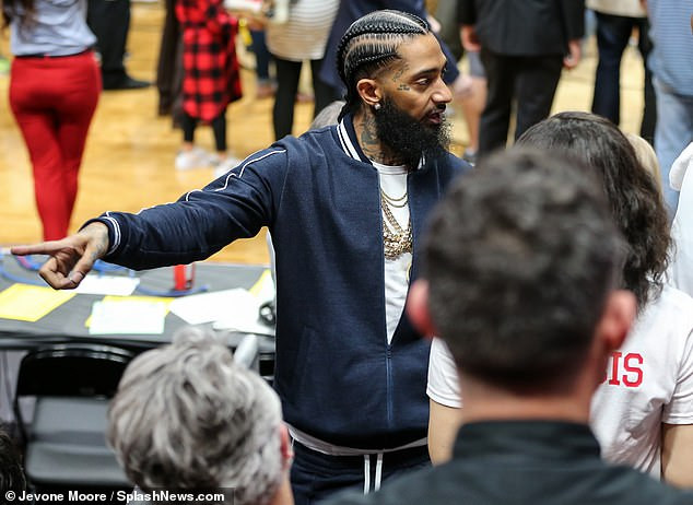 Photo of slain rapper Nipsey Hussle posing with a fan