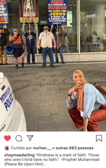 Muslim woman goes viral as she defies anti-Muslim protesters by taking smiling photo in front of them