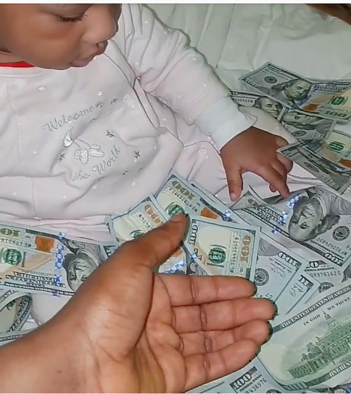Ehi Ogbebor shows off the wads of Dollars and Nairas that rained at her daughter