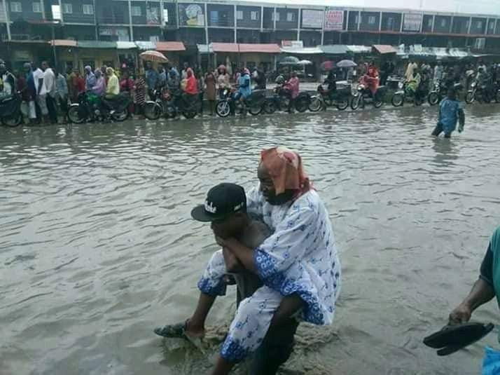 Photos: Commuters are paying touts N100 to carry them on their backs across the flooded road at Trade Fair Complex, along Lagos- Badagry Express