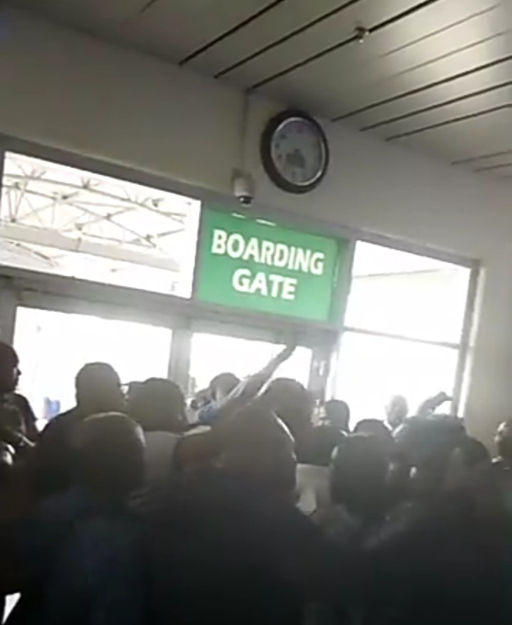 Chaos at Abuja airport as angry passengers stranded since morning disrupt other passengers from boarding (video)