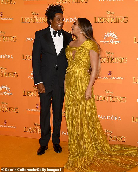 Beyonc? commands attention in a gold asymmetric gown as she joins husband Jay-Z at London